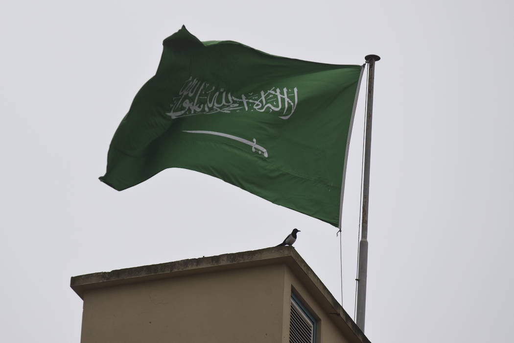 A bird sits by a Saudi Arabia's flag on the roof top of Saudi Arabia's consulate in Istanbul, Sunday, Oct. 14, 2018. Writer Jamal Khashoggi vanished after he walked into the consulate on Oct. 2. ( ...
