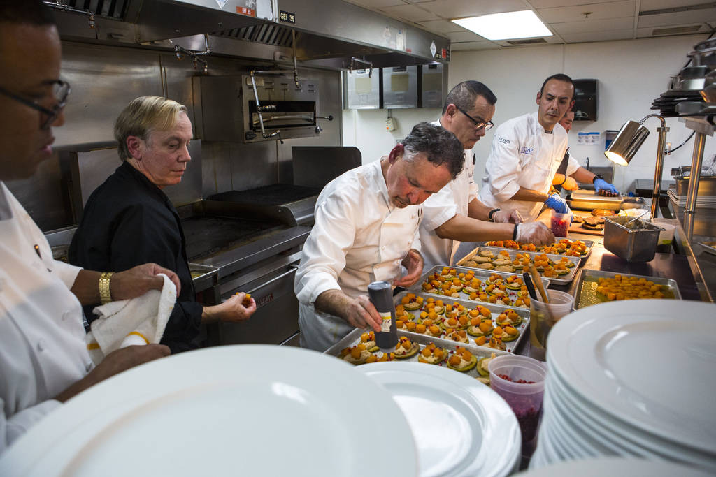 Chef Stephan Pyles, center, prepares the 6th course dish with assistance from Chef Jimmy Schmidt, left, in the kitchen during the James Beard Foundation's Celebrity Chef tour dinner series at the ...