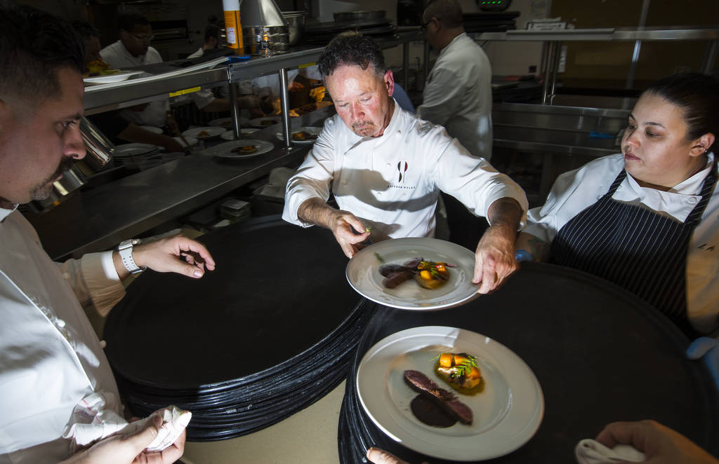Chef Stephan Pyles, center, plates the 6th course dish in the kitchen during the James Beard Foundation's Celebrity Chef tour dinner series at the Velvet Room at Luxor in Las Vegas on Saturday, Oc ...