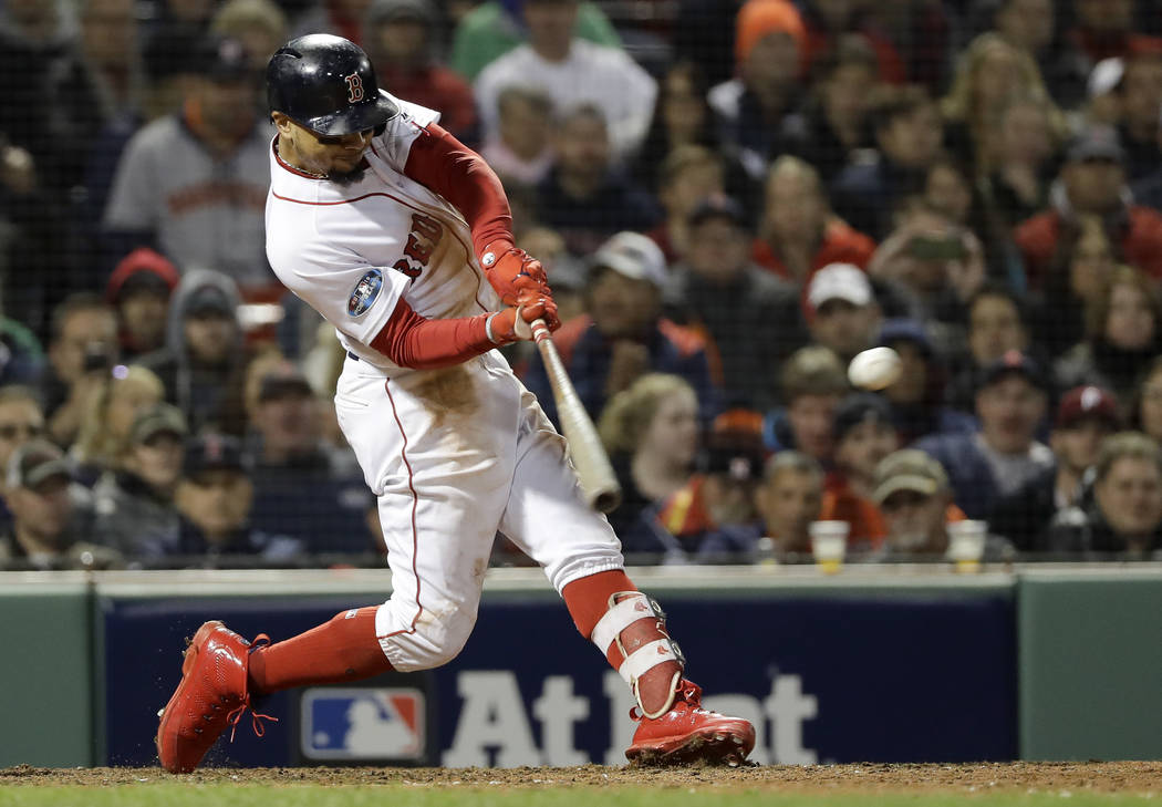 Boston Red Sox's Mookie Betts hits a RBI-double against the Houston Astros during the eighth inning in Game 2 of a baseball American League Championship Series on Sunday, Oct. 14, 2018, in Boston. ...