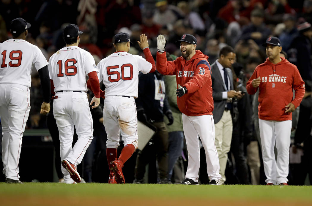 Members of the Boston Red Sox celebrate after their 7-5 win against the Houston Astros in Game 2 of a baseball American League Championship Series on Sunday, Oct. 14, 2018, in Boston. (AP Photo/Ch ...