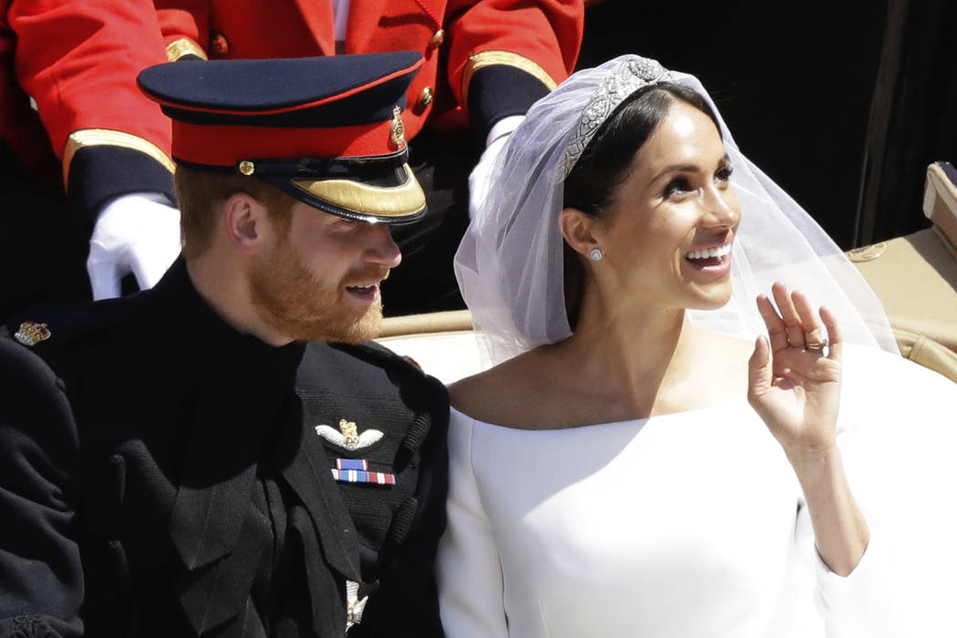 In this Saturday, May 19, 2018 file photo, Britain's Prince Harry and Meghan Markle wave as they leave Windsor Castle in a carriage after their wedding ceremony at St. George's Chapel in Windsor C ...