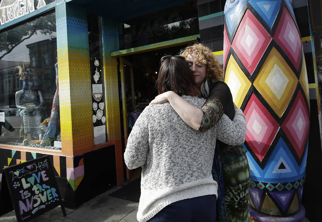 Sunshine Powers, owner of the store Love on Haight, right, hugs Christin Evans, owner of The Booksmith, outside of Powers' store in San Francisco, on Oct. 1, 2018. (AP Photo/Jeff Chiu)