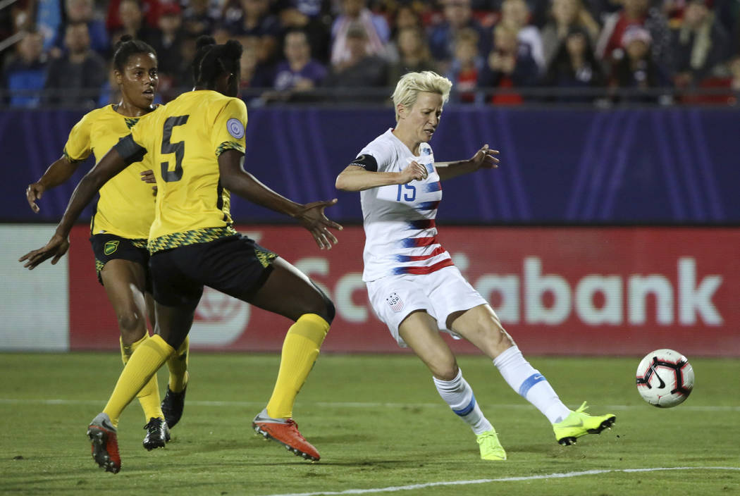 United States forward Megan Rapinoe scores a goal while being defended by Jamaica defender Konya Plummer during the first half of a CONCACAF women's World Cup qualifying tournament soccer match in ...