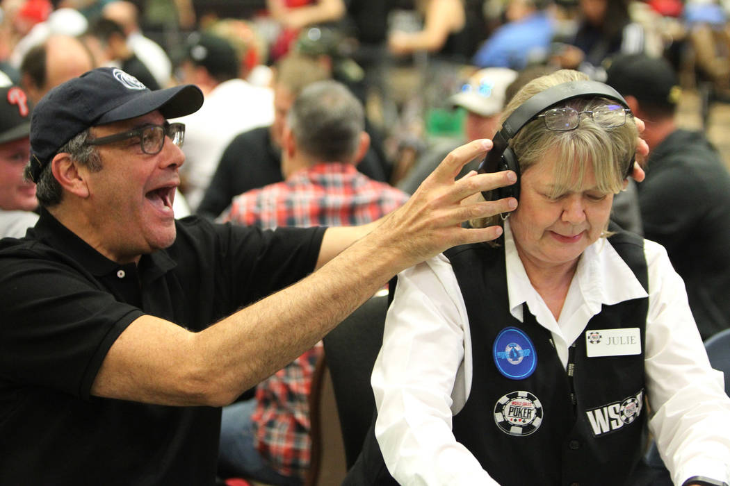 Comedian Brad Garrett, left, holds his headphones over the ears of his table dealer Julie Fosdick as he competes during Day 1C of the World Series of Poker event at the Rio Convention Center in La ...