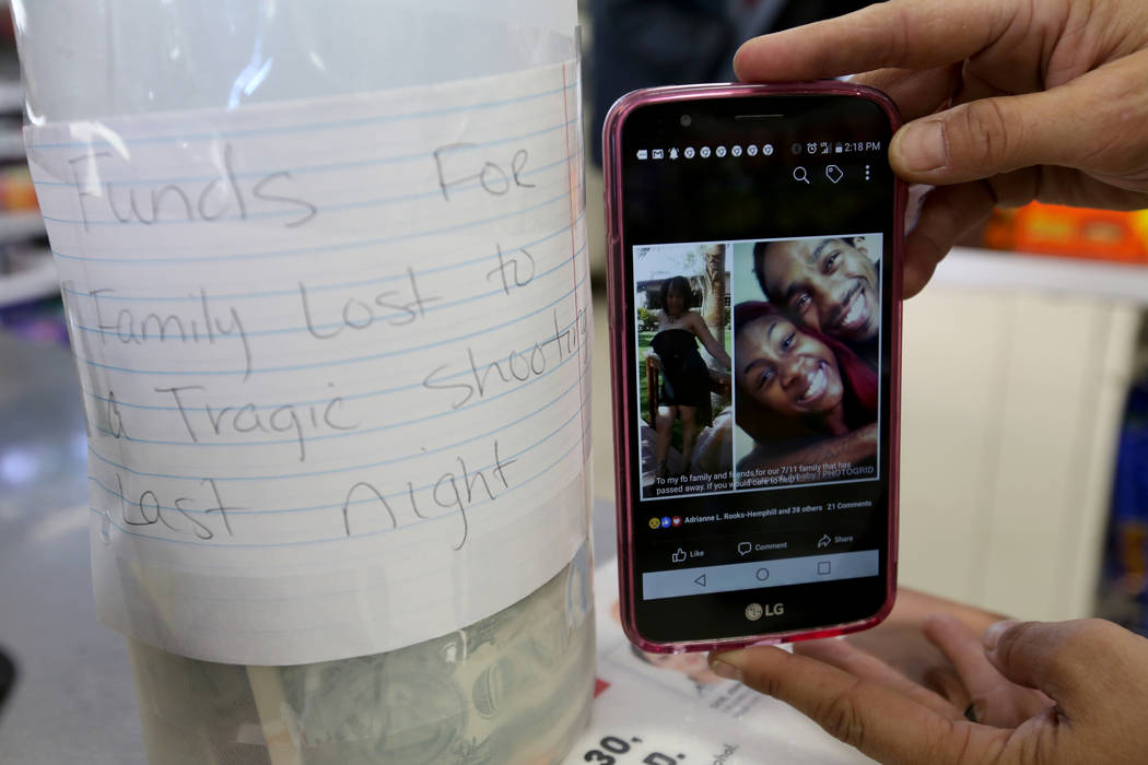 A 7-eleven employee shows a photo Monday, Oct. 15, 2018, of who she said are victims of a triple homicide Sunday night near the store at West Lake Mead Boulevard and Simmons Street in North Las Ve ...