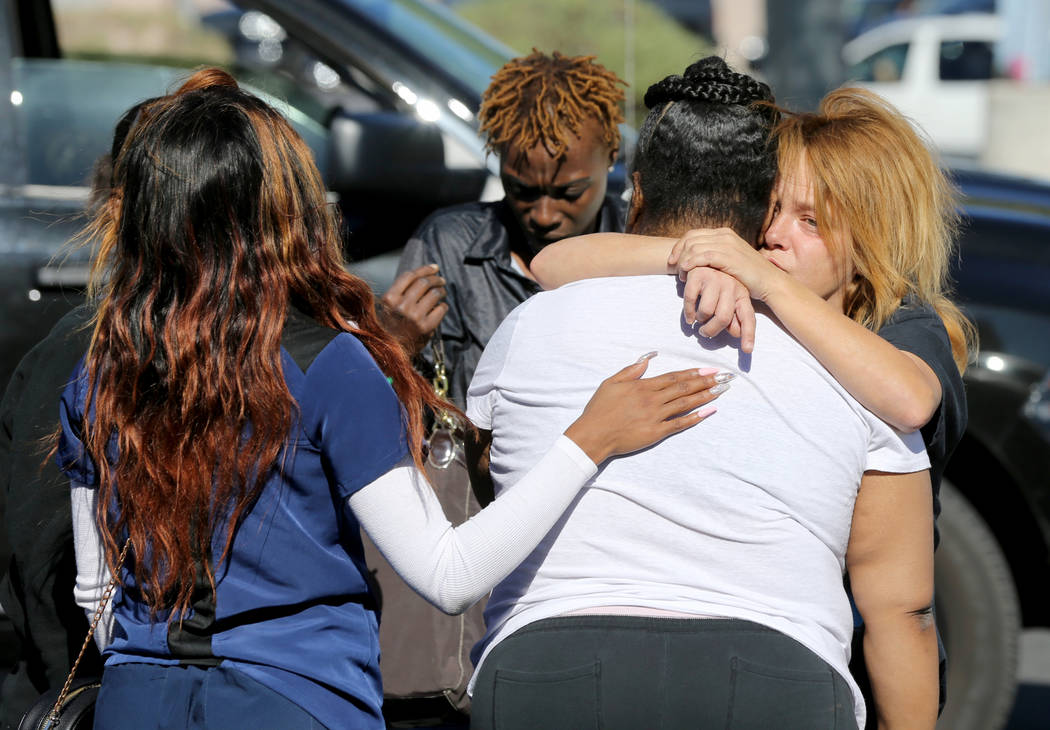 Employees of 7-eleven and friends comforts a woman Monday, Oct. 15, 2018, who was identified as the sister of a triple homicide Sunday night near the store at West Lake Mead Boulevard and Simmons ...