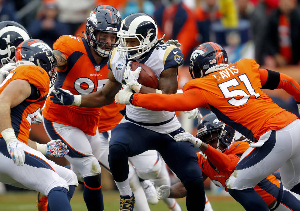 Los Angeles Rams running back Todd Gurley (30) runs as Denver Broncos linebacker Todd Davis (51) and defensive end Derek Wolfe (95) defend during the second half of an NFL football game, Sunday, O ...