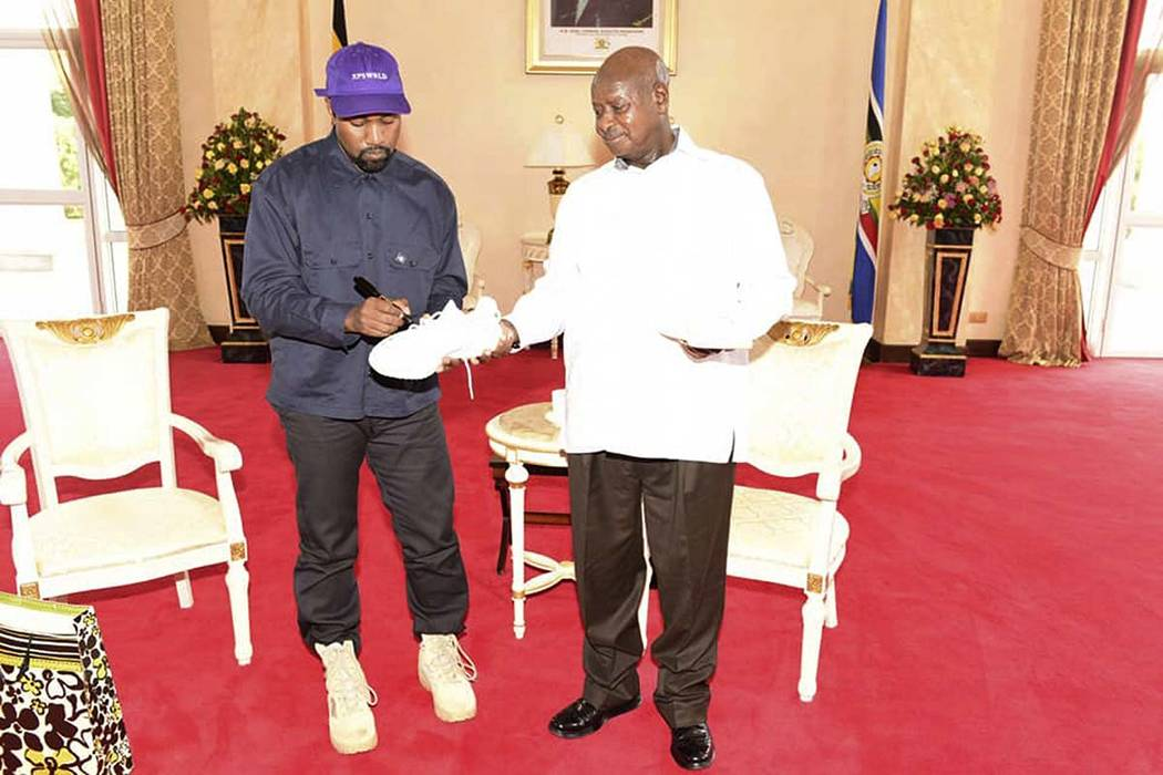 "Kanye West autographs a pair of his sneakers as a gift to Uganda's President Yoweri Museveni, right, on Monday, Oct. 15, 2018, in Entebbe, Uganda. Museveni said he and West held ""fruitful discussi ..."