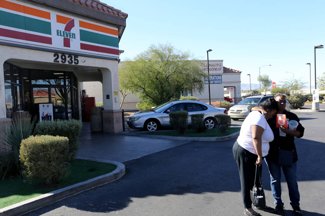 A 7-Eleven employee, right, comforts a woman Monday, Oct. 15, 2018, who was identified as the sister of a triple homicide Sunday night near the store at West Lake Mead Boulevard and Simmons Street ...