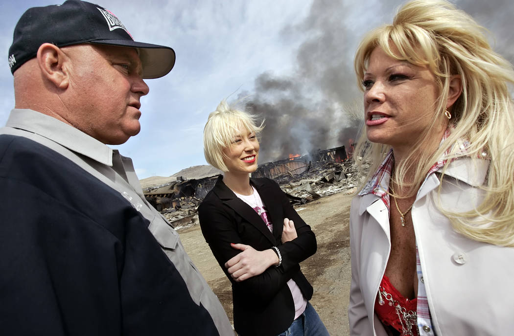 "Moonlite Bunny ranch brothel owner Dennis Hof, left, talks with two of his employees, Brooke Taylor, center, and a woman who identified herself as ""Air Force Amy"" as the remains of the f ..."