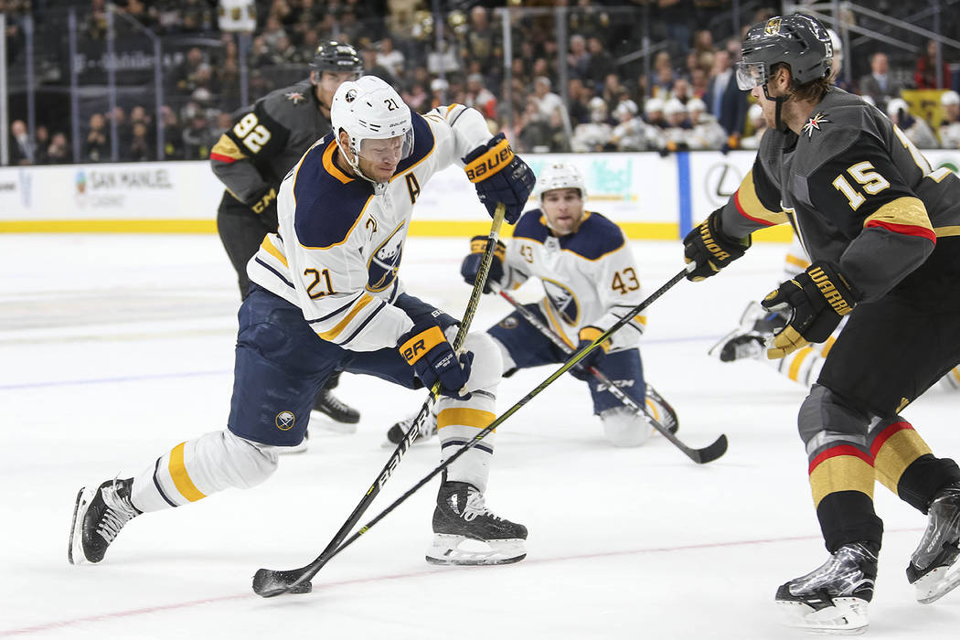 Buffalo Sabres right wing Kyle Okposo (21) takes a shot as Vegas Golden Knights defenseman Jon Merrill (15) defends during the third period of an NHL hockey game at T-Mobile Arena in Las Vegas, Tu ...