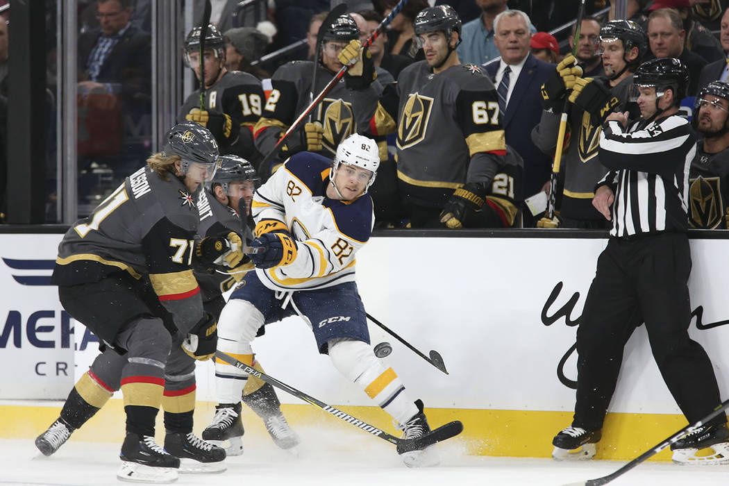 Buffalo Sabres defenseman Nathan Beaulieu (82) passes the puck past Vegas Golden Knights center William Karlsson (71) during the first period of an NHL hockey game at T-Mobile Arena in Las Vegas, ...