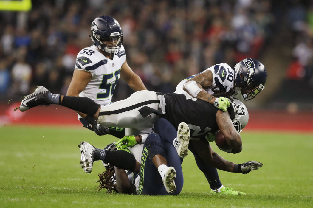 Oakland Raiders running back Marshawn Lynch (24) is halted by the Seattle Seahawks defense during the first half of an NFL football game at Wembley stadium in London, Sunday, Oct. 14, 2018. (AP Ph ...