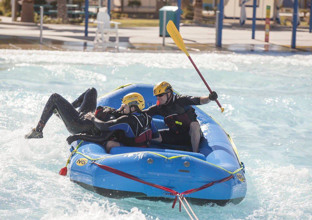 """Engineer Kevin Flynn, right, and Firefighter Tim McKeever Junior, center, rescue """"victim"""" Firefighter Ian Bradley during swift water rescue training with a new raft at Cowabunga Bay in H ..."""