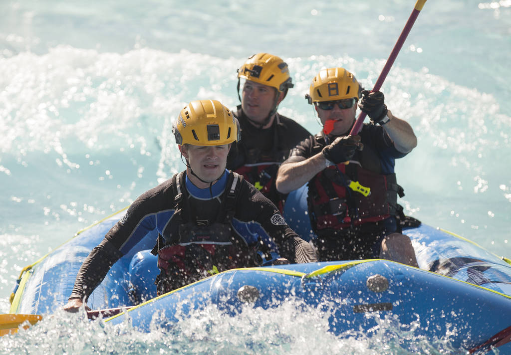 """Firefighter Tim McKeever Junior, from left, """"victim"""" Firefighter Ian Bradley, and Engineer Kevin Flynn, return the raft to shore during swift water rescue training at Cowabunga Bay in He ..."""
