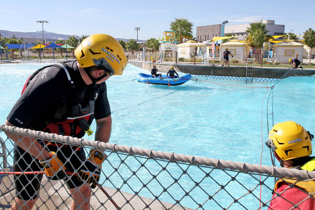 Firefighters from Station 82 maneuver a new raft for swift water rescue training at Cowabunga Bay in Henderson, Wednesday, Oct. 17, 2018. It will be used to rescue people trapped in the water in f ...