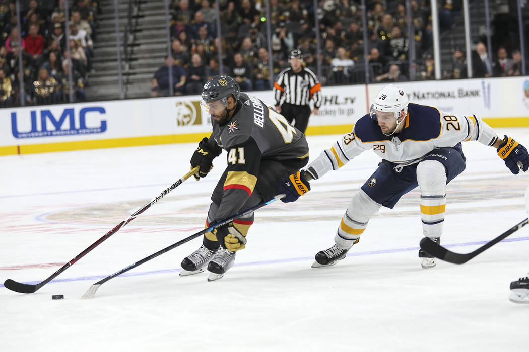 Vegas Golden Knights left wing Pierre-Edouard Bellemare (41) keeps the puck away from Buffalo Sabres center Zemgus Girgensons (28) during the second period of an NHL hockey game at T-Mobile Arena ...