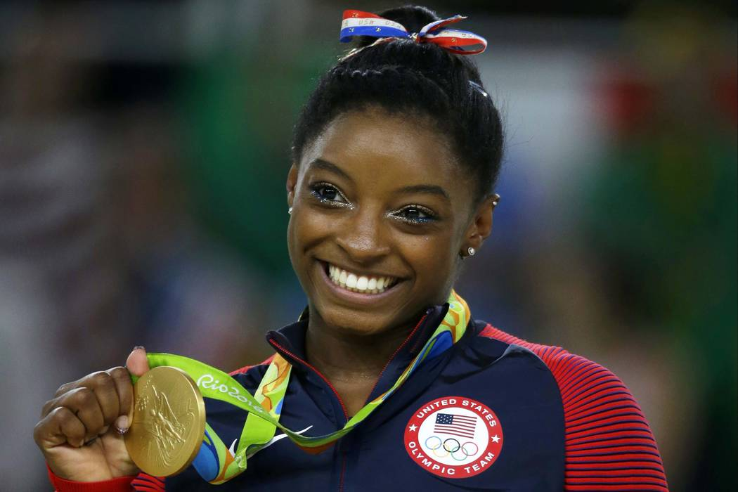 United States gymnast Simone Biles displays her gold medal for floor during the artistic gymnastics women's apparatus final at the 2016 Summer Olympics in Rio de Janeiro, Brazil, Aug. 16, 2016. I ...