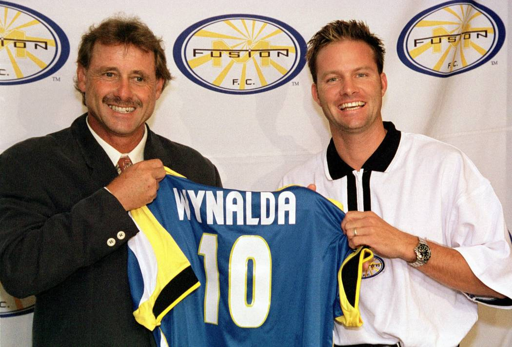 Miami Fusion coach Ivo Wortmann, left, and U.S. National Team star forward Eric Wynalda show Wynalda's new Fusion jersey during a press conference in Miami, Thursday June 3, 1999. The Miami Fusion ...