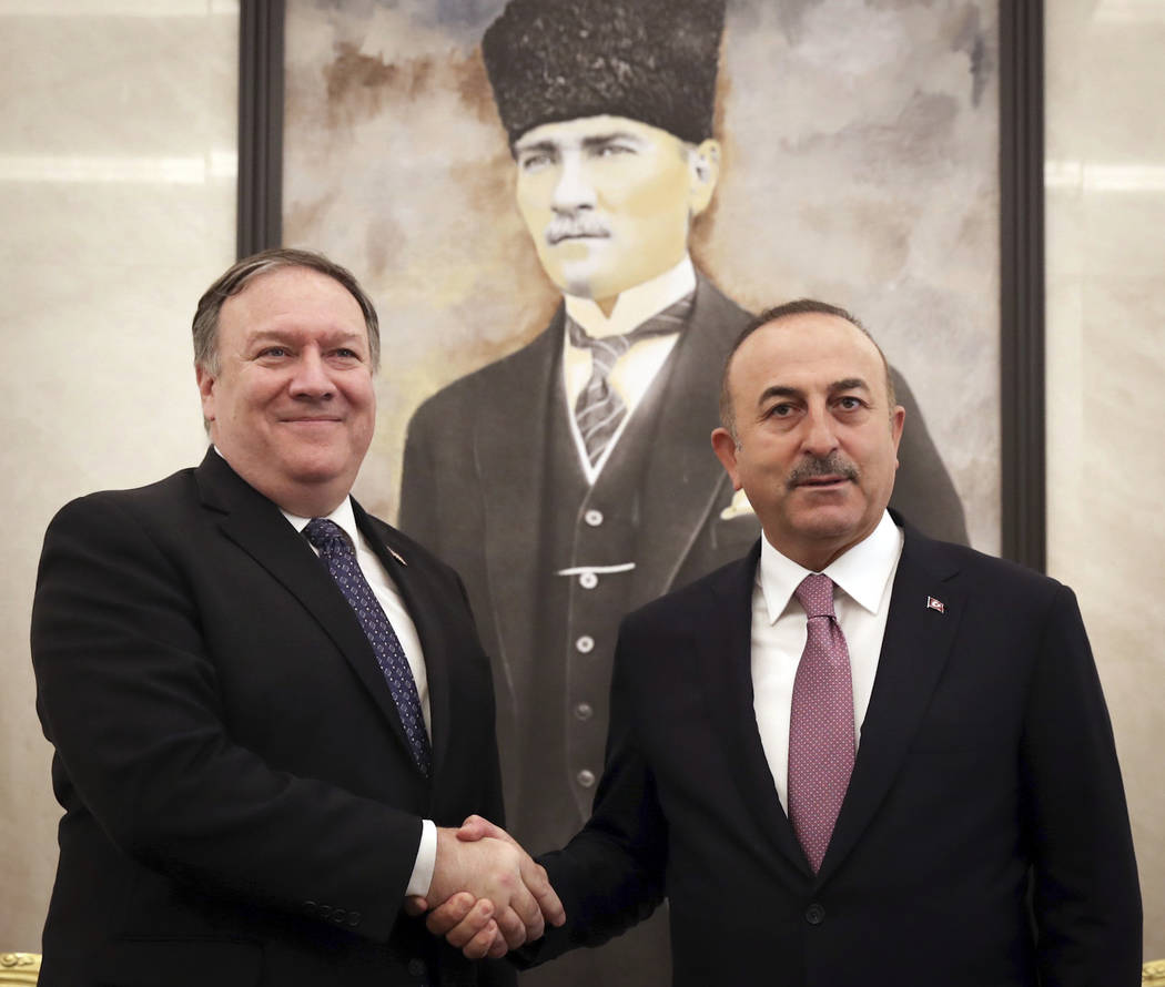 Turkey's Foreign Minister Mevlut Cavusoglu, right, and U.S. Secretary of State Mike Pompeo shake hands before a meeting at the Esenboga Airport in Ankara, Turkey, Wednesday, Oct. 17, 2018. Pro-gov ...