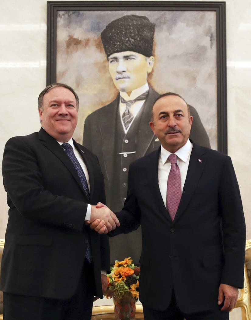 Turkey's Foreign Minister Mevlut Cavusoglu, right, and U.S. Secretary of State Mike Pompeo shake hands before a talks at the Esenboga Airport in Ankara, Turkey, Wednesday, Oct. 17, 2018. Pro-gover ...