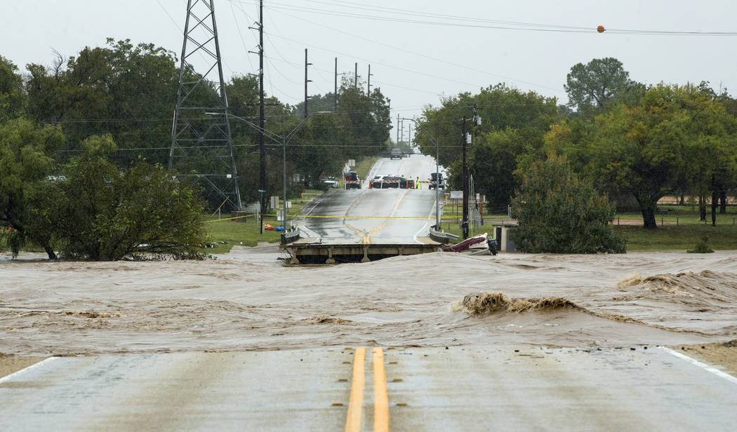 The Llano River flows between to sides of Ranch Road 2900 after the bridge was washed out due to flooding Tuesday, Oct. 16, 2018, in Kingsland, Texas. (Jay Janner/Austin American-Statesman via AP)