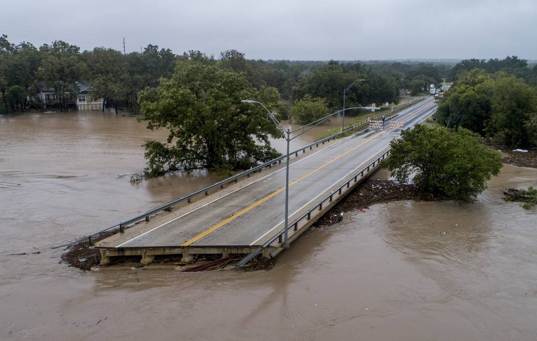 The Llano River flows past one sides of Ranch Road 2900 bridge after the bridge was washed out due to flooding Tuesday, Oct. 16, 2018, in Kingsland, Texas. (Jay Janner/Austin American-Statesman vi ...