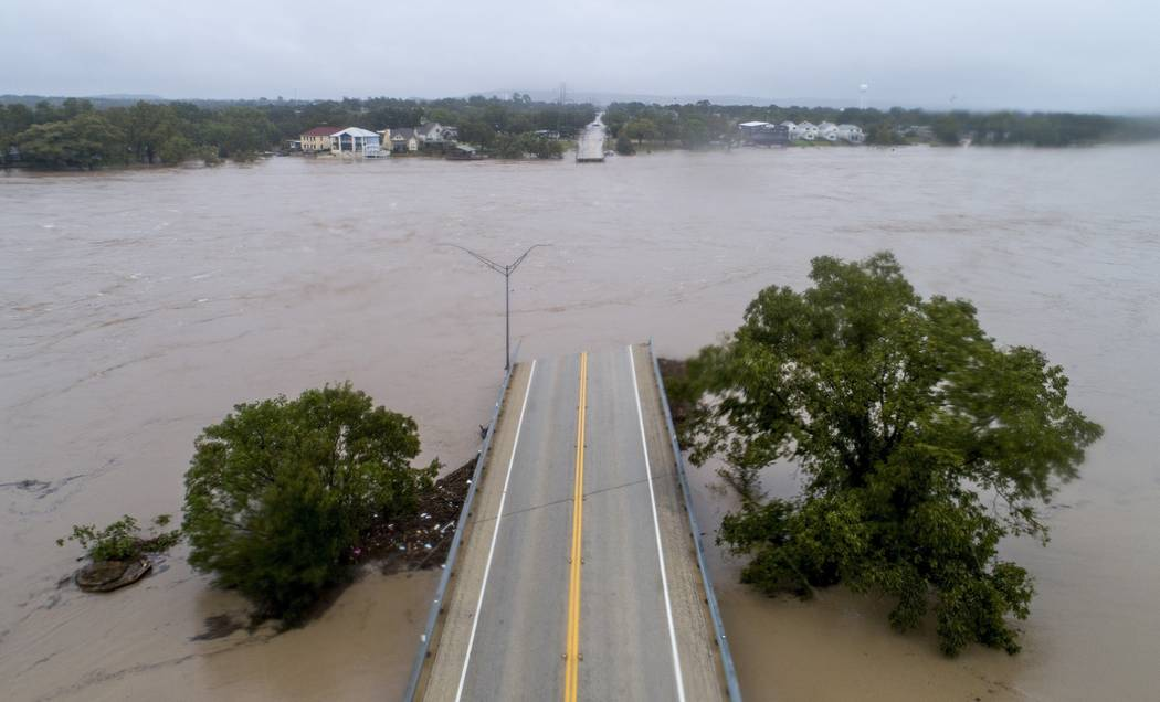The Llano River flows between the washed out Ranch Road 2900 bridge, Tuesday, Oct. 16, 2018, in Kingsland, Texas. (Jay Janner/Austin American-Statesman via AP)