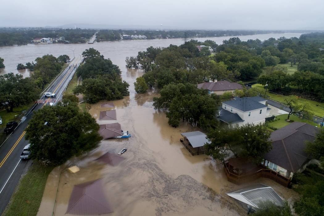 The Llano River overflows its banks into neighboring property as the swollen river flows between the washed out Ranch Road 2900 bridge, background, Tuesday, Oct. 16, 2018, in Kingsland, Texas. (Ja ...