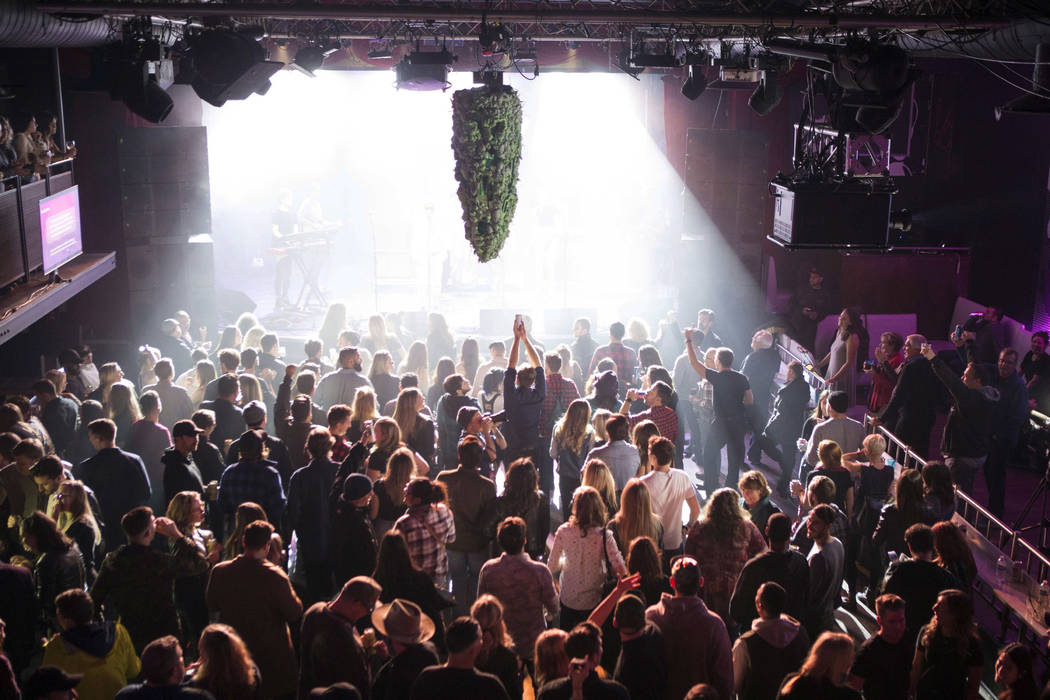 A depiction of a cannabis bud hangs from the ceiling as a band plays at Leafly's countdown party in Toronto, Tuesday, Oct. 16, 2018, as they prepare to mark the legalization of Cannabis across Can ...