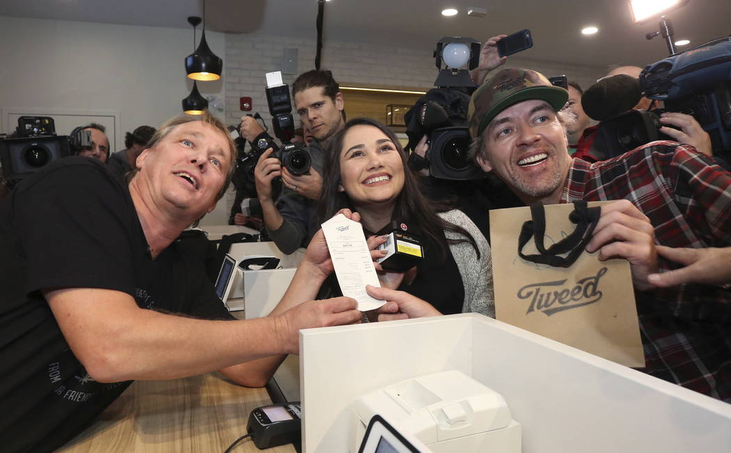 Canopy Growth CEO Bruce Linton, left to right, poses with the receipt for the first legal cannabis for recreation use sold in Canada to Nikki Rose and Ian Power at the Tweed shop on Water Street i ...