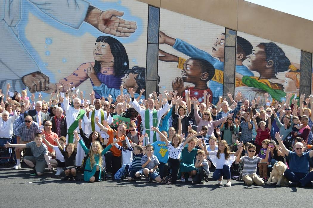 Pastor Brad Beckman and members of the First Good Shepherd Lutheran church congregation pose with artist Heather Toledo in front of the mural she painted for their church doing a dedication on Sun ...