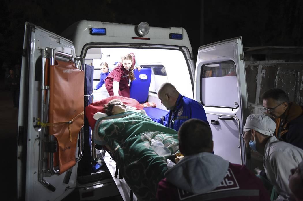 Medics load an injured person onto an ambulance, in Kerch, Crimea, Wednesday Oct. 17, 2018. (Viktor Korotaev/Kommersant Photo via AP)