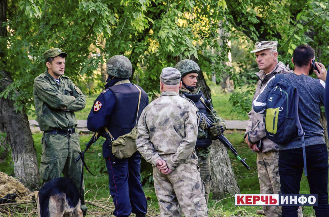 Policemen stand near the vocational college, in Kerch, Crimea, Wednesday Oct. 17, 2018. An explosive device has killed several people and injured at least 50 others at a vocational college in Crim ...