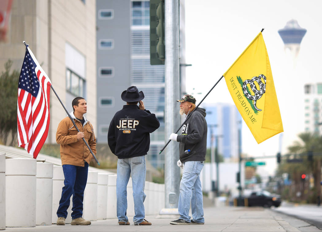 Joshua Martinez, left, Greg Whalen, center, and Michael Elliot, stand outside of the Lloyd D. George Courthouse to demonstrate their support for the Bundy family in Las Vegas on Friday, Dec. 9, 20 ...