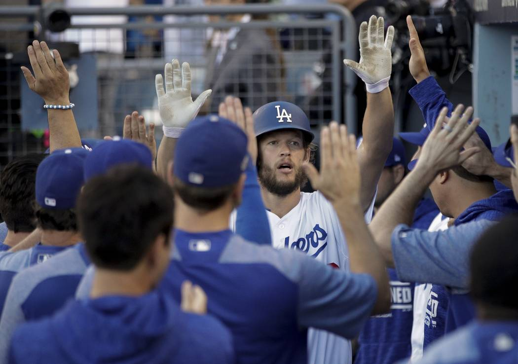 Los Angeles Dodgers' Clayton Kershaw is congratulated after scoring a run during the seventh inning of Game 5 of the National League Championship Series baseball game against the Milwaukee Brewers ...