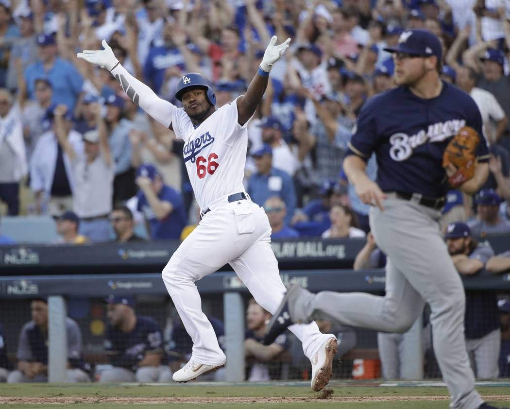 Los Angeles Dodgers' Yasiel Puig reacts after hitting an RBI single during the sixth inning of Game 5 of the National League Championship Series baseball game against the Milwaukee Brewers Wednesd ...