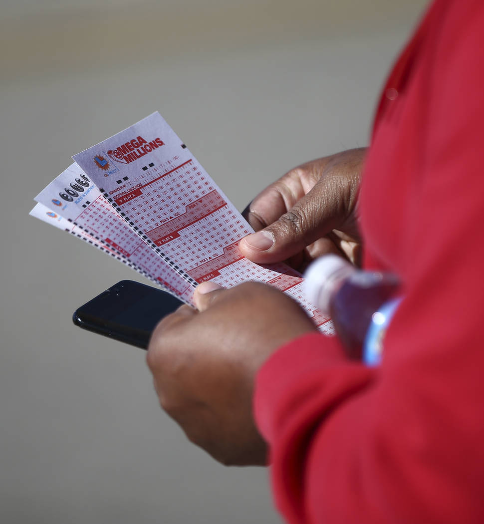 A man holds a Mega Millions form as hundreds line up outside of the Primm Valley Lotto Store as people wait to buy the Mega Millions lottery tickets in Primm on Thursday, Oct. 18, 2018. Chase Stev ...
