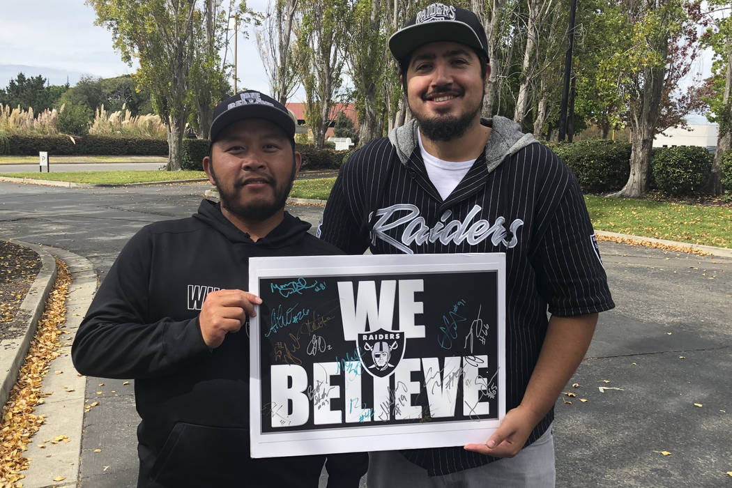 Raiders fans Hein Tu, left, and Jose Valenzuela hold a player-autographed sign while standing outside team headquarters on Oct. 1, 2018. (Michael Gehlken/Las Vegas Review-Journal)