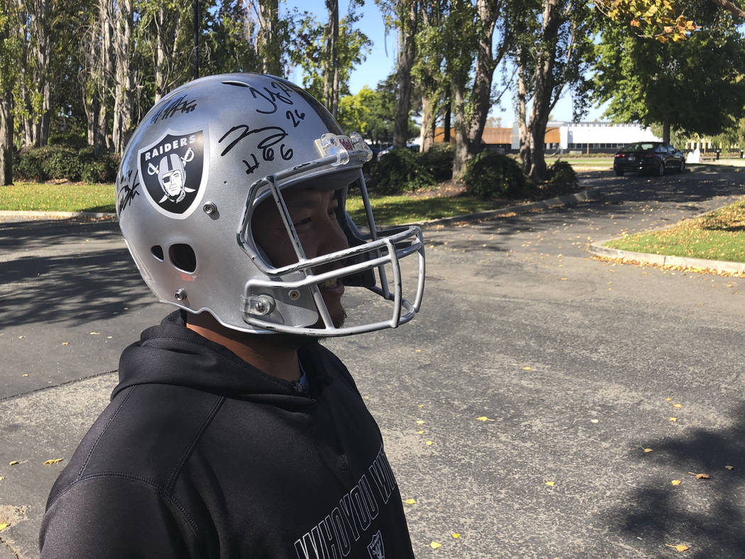 Raiders fan Hein Tu wears a player-autographed helmet while standing outside team headquarters on Sept. 24, 2018. (Michael Gehlken/Las Vegas Review-Journal)