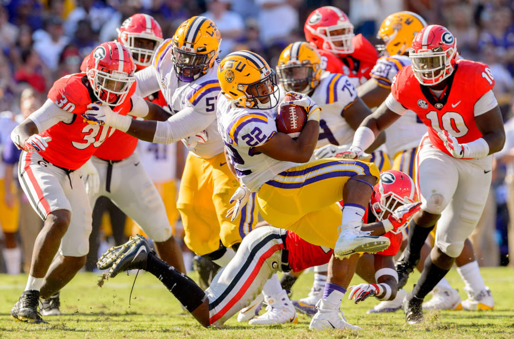 LSU running back Clyde Edwards-Helaire (22) spins around Georgia defenders during the first half of an NCAA college football game in Baton Rouge, La., Saturday, Oct. 13, 2018. (AP Photo/Matthew Hi ...
