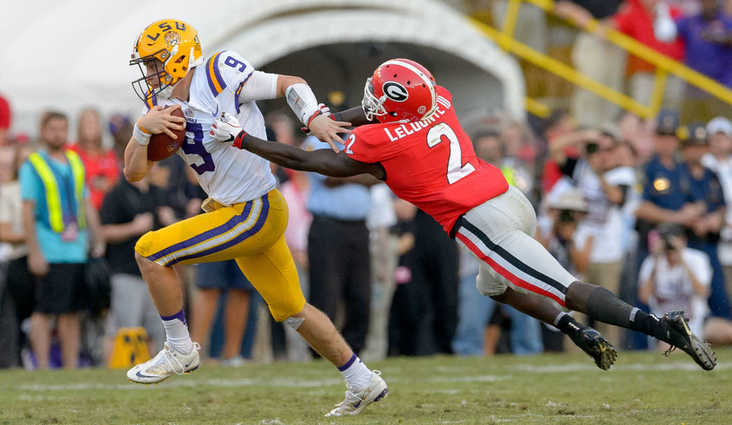 LSU quarterback Joe Burrow (9) begins a 59 yard run against Georgia defensive back Richard LeCounte (2) during the second half of an NCAA college football game in Baton Rouge, La., Saturday, Oct. ...