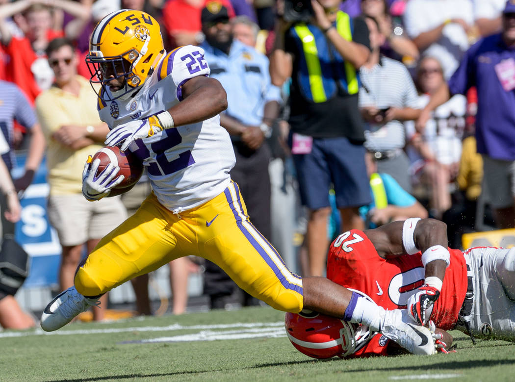LSU running back Clyde Edwards-Helaire (22) runs against Georgia defensive back J.R. Reed (20) in an NCAA college football game in Baton Rouge, La., Saturday, Oct. 13, 2018. (AP Photo/Matthew Hinton)