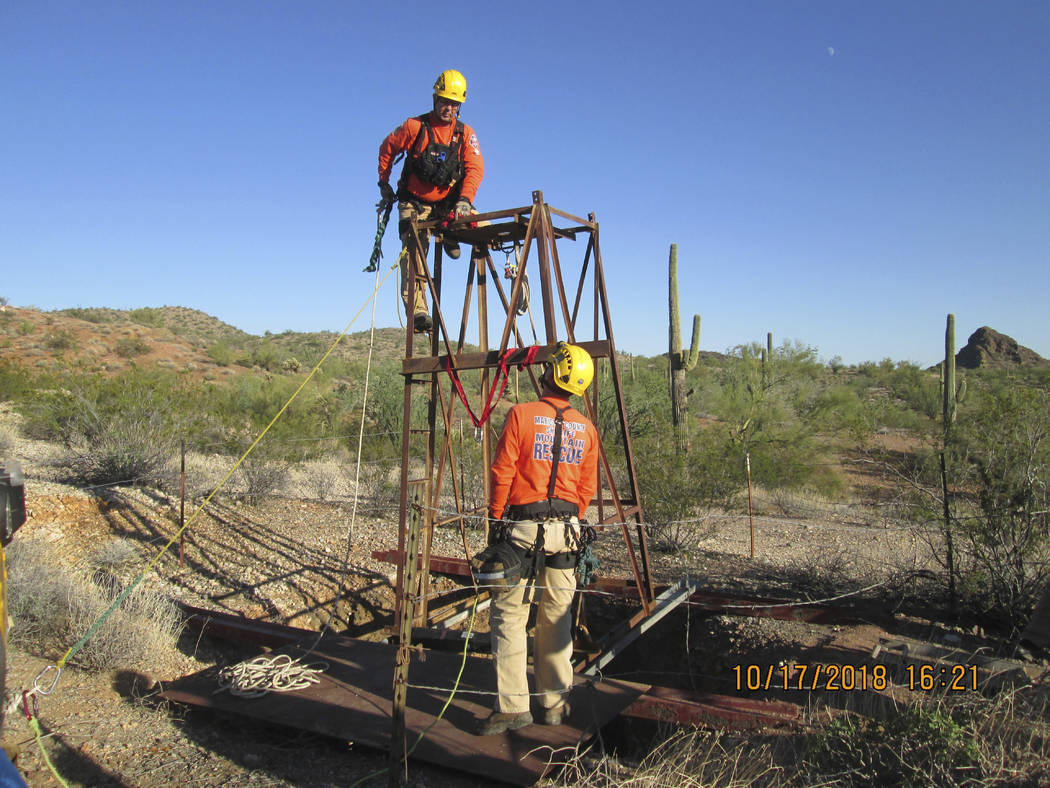 This Oct. 17, 2018 photo provided by the Maricopa County Sheriff's Office shows a Maricopa County Mountain Rescue team prepare to rescue a man who fell into an old abandoned mine shaft near Aguila ...