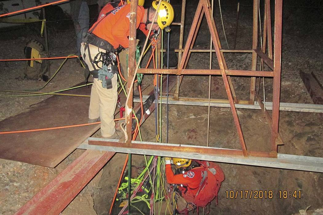 A rescue team on Wednesday, Oct. 17, 2018, lowers themselves into an abandoned mine shaft to rescue a man who fell into the shaft on Monday, Oct. 15, 2018, the near Aguila, Ariz. (Maricopa County ...