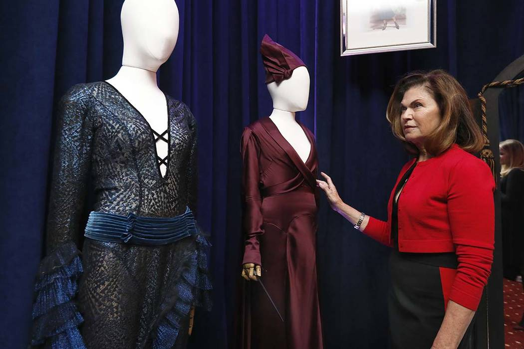 """Colleen Atwood appears with two of her designs from """"Fantastic Beasts: The Crimes of Grindelwald,"""" during a preview of the Neiman Marcus Christmas Book in New York, Thursday, Oct. 18, 2018. The O ..."""