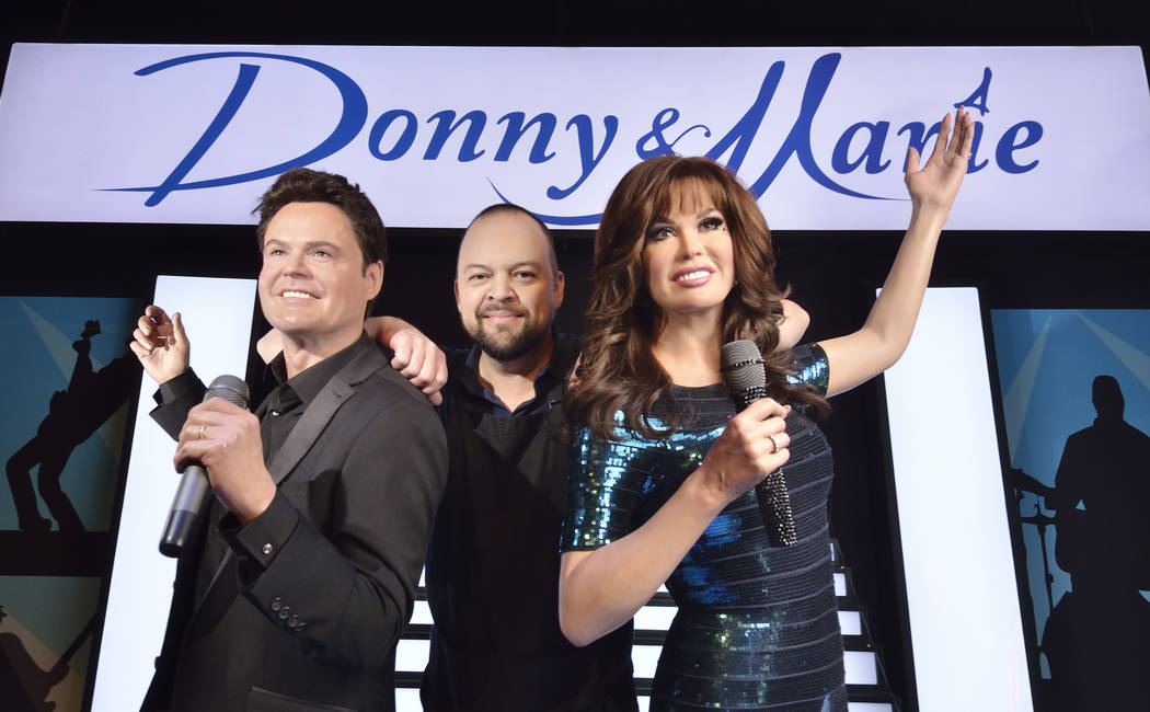 """Lead studio artist Adam Morey strikes a pose with pals Donny and Marie Osmond -- their wax versions, anyway -- in Madame Tussauds """"Viva Las Vegas"""" room. Bill Hughes/Las Vegas Review-Journal"""