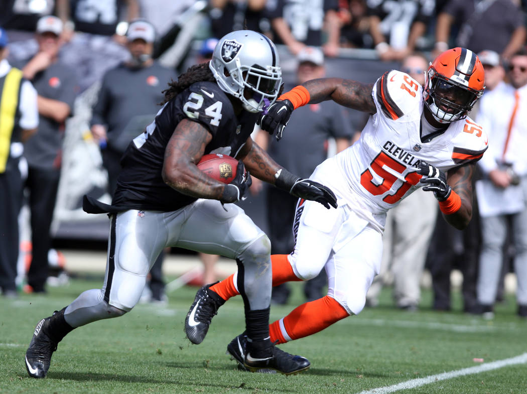 Oakland Raiders running back Marshawn Lynch (24) runs past Cleveland Browns outside linebacker Jamie Collins (51) during the first half of their NFL game in Oakland, Calif., Sunday, Sept. 30, 2018 ...