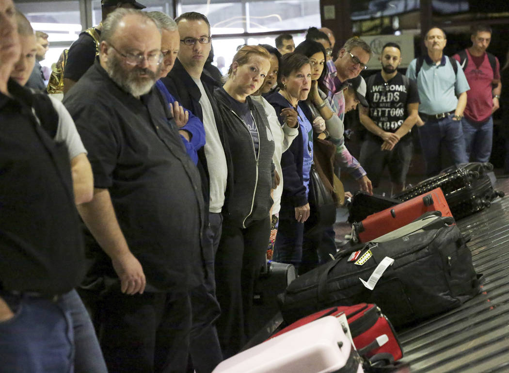 Travelers watch for their luggage on the baggage claim carousel in McCarran International Airport, which just received a top ranking for quality from J.D. Power & Associates, Friday, Oct. 19, 2018 ...